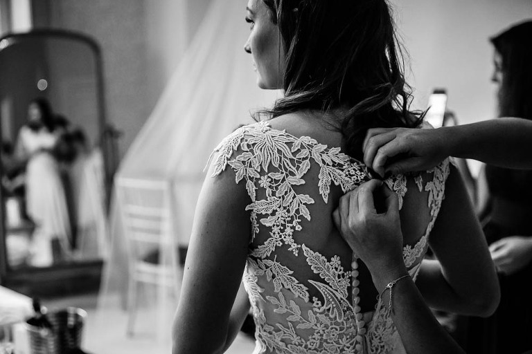 Wedding Dress Detail, bride putting on wedding dress shot at Nonsuch Mansion by Stylish Wedding Photography